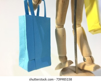Wooden human mannequin carries shopping bags in different postures. Shop until drop. Apply to concept of holiday shopping and online shopping. White background. Blur background.