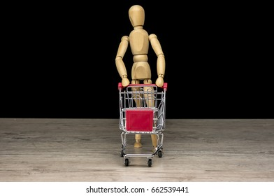 Wooden human mannequin holding shopping trolley close up