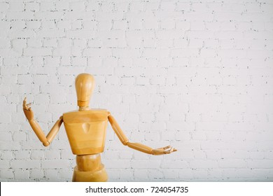 Wooden human on white brick backgroung with copy space