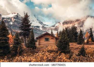 Wooden hut with Assiniboine mountain in autumn forest at provincial park, Canada