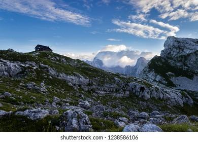 Wooden hut and blue sky in the valley of Triglav National Park. Slovenia, Triglav region. Julian Alps. Slovenian Alps mountains. Summer time.