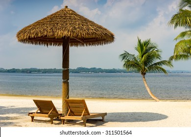 Wooden hut and chairs at beach with beautiful blue sky