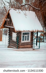 wooden hut covered with snow
