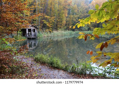 Wooden hut on the lake in the autumn forest