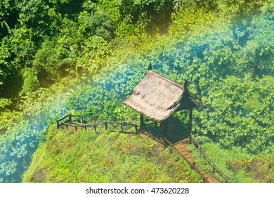 Wooden hut with rainbow from waterfall in forest.