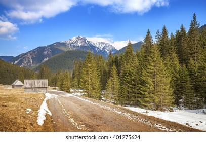 Wooden huts by a dirt road in Tatra Mountains, end of winter and beginning of spring, Poland.