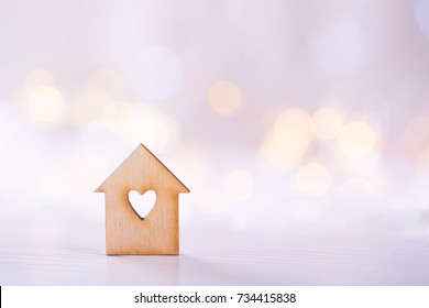 Wooden icon of house with hole in the form of heart on light bokeh background. Romantic card. Concept of sweet home.