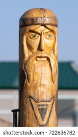 Wooden idol of Slavic culture on village estate background