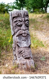 Wooden idol of Slavic god by a path in the forest. Forest in the background.