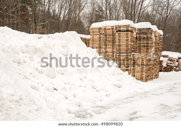 Wooden industrial pallets stacked with snow