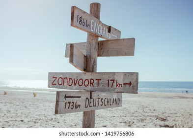 Wooden information board with distance to England, Germany and Zandvoort on the beach by the North Sea in Noordwijk, The Netherlands