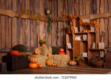 Wooden interior with pumkins, autumn leaves and flowers. Halloween and thanksgiving decoration.