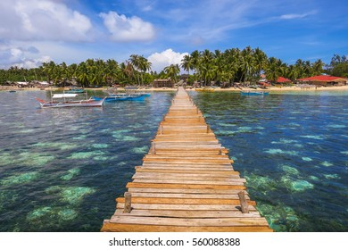 Wooden Island Pier Stretching Over Turquoise Sea, With Tropical Fishing Village and Boats - General Luna, Siargao - Philippines