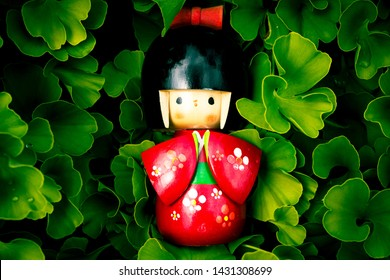 Wooden Japanese Kokeshi Doll dressed in traditional kimono on ginkgo biloba leaves background,  hand painted in red and florals