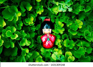 Wooden Japanese Kokeshi Doll dressed in traditional kimono on ginkgo biloba leaves pattern background,  hand painted in red and florals