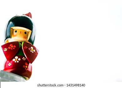 Wooden Japanese Kokeshi Doll dressed in traditional kimono over white background, hand carved and painted