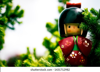 Wooden Japanese Kokeshi Doll dressed in traditional kimono, hidden between pine branches,  hand painted in red and florals