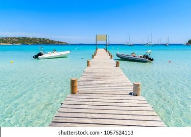 Wooden jetty with boats on Santa Giulia beach, Corsica island, France