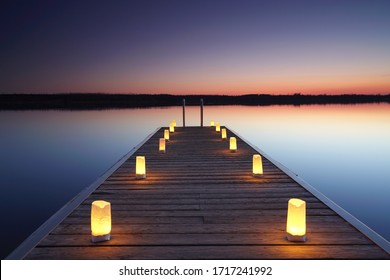 wooden jetty with burning candles, romantic place at the beach