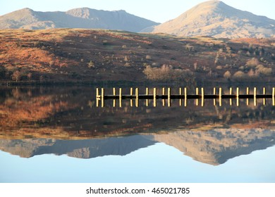 A wooden jetty crosses the reflection of a Lakeland mountain on Coniston water in winter