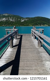 Wooden jetty and distant mountains on the turquoise waters of Lake Annecy France
