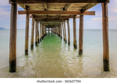 Wooden jetty extending into the sea. Photograph taken from underneath.