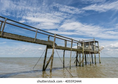 Wooden jetty for fishing in the Gironde Medoc France with blue sky and white clouds.