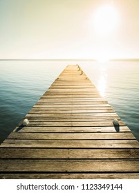 Wooden jetty with golden light as background