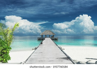 wooden jetty leading to a cabana on a beautiful untouched tropical beach