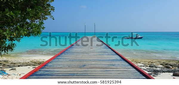 Wooden jetty on the beach with a beautiful blue sea sky background