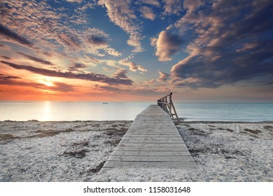 wooden jetty on beatiful beach - romantic place in sunset