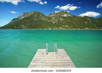 wooden jetty on the lake, turquoise water on mountain lake
