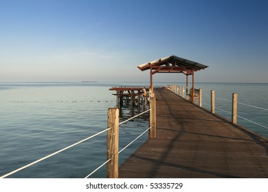 wooden jetty on mabul island looking across the ocean to sipdan island on the horizon sabah malaysian borneo