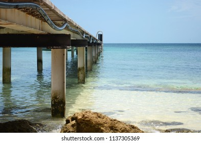 A wooden jetty, seen from below, extends over rocks into clear pale blue water. Rocks and sand can be seen through the water. The sky is clear and blue.