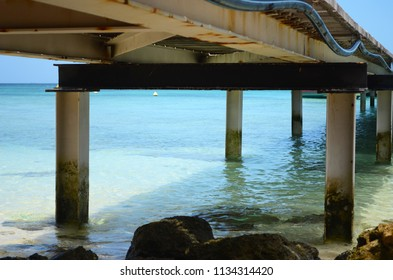 A wooden jetty is seen from below. It is surrounded by translucent pale blue water. Some rocks are in the foreground.