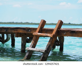 Wooden jetty swimming dock steps into the beautiful blue water at lake bacalar Mexico