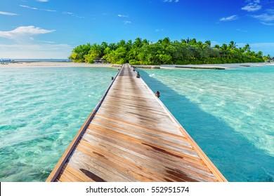 Wooden jetty towards a small island on Indian Ocean, Maldives. Sunny blue sky.