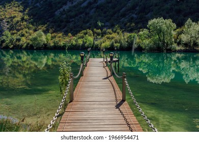Wooden jetty in transparent water lake between mountains