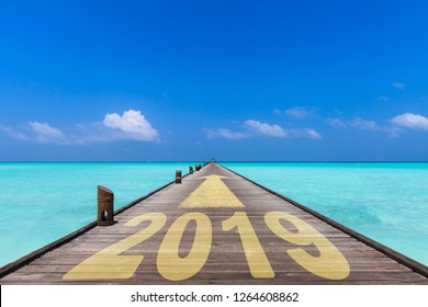 wooden jetty with the word 2019 and an yellow arrow showing forward to the horizon, business concept for turn of the year