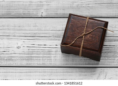 Wooden jewelry box on wooden white background. Gift tied with a rope. Empty space, free space