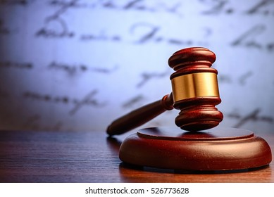 Wooden judge or auctioneers gavel on a plinth with a defocused background of a hadwritten document conceptual of justice and sentencing