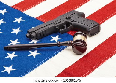 Wooden judge gavel and black color gun over USA flag