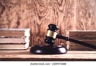 Wooden judge gavel and books on wooden desk. Law and Justice