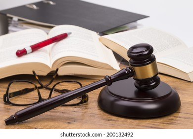 Wooden judge gavel and books on a wooden table