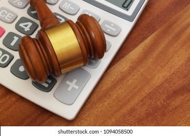 Wooden judge gavel and calculator