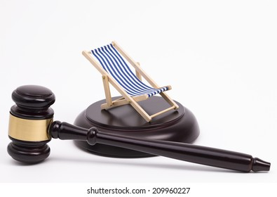 Wooden judge gavel and a deck chair isolated on white background