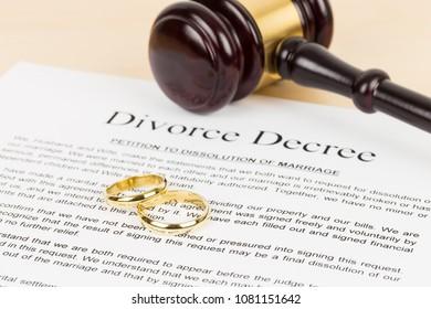 Wooden judge gavel, golden rings, and divorce decree; document is mock-up
