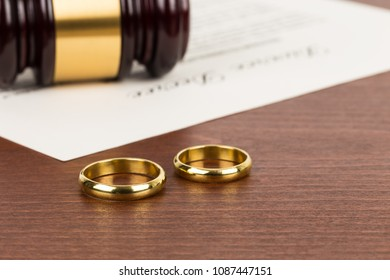 Wooden judge gavel, golden rings, and divorce decree; document is mock-up