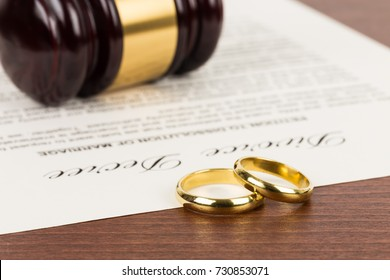 Wooden judge gavel, golden rings, and divorce decree: document is mock-up