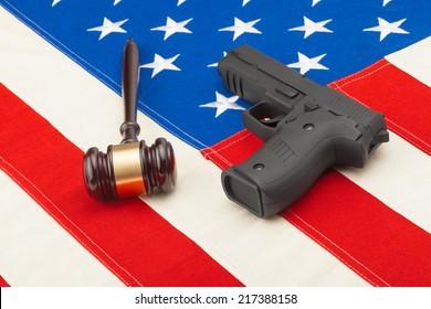 Wooden judge gavel and gun over USA flag - studio shot